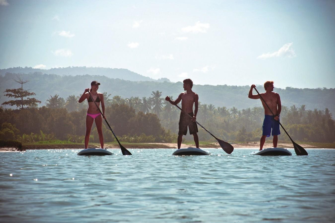 Young boys paddleboard at Nihiwatu