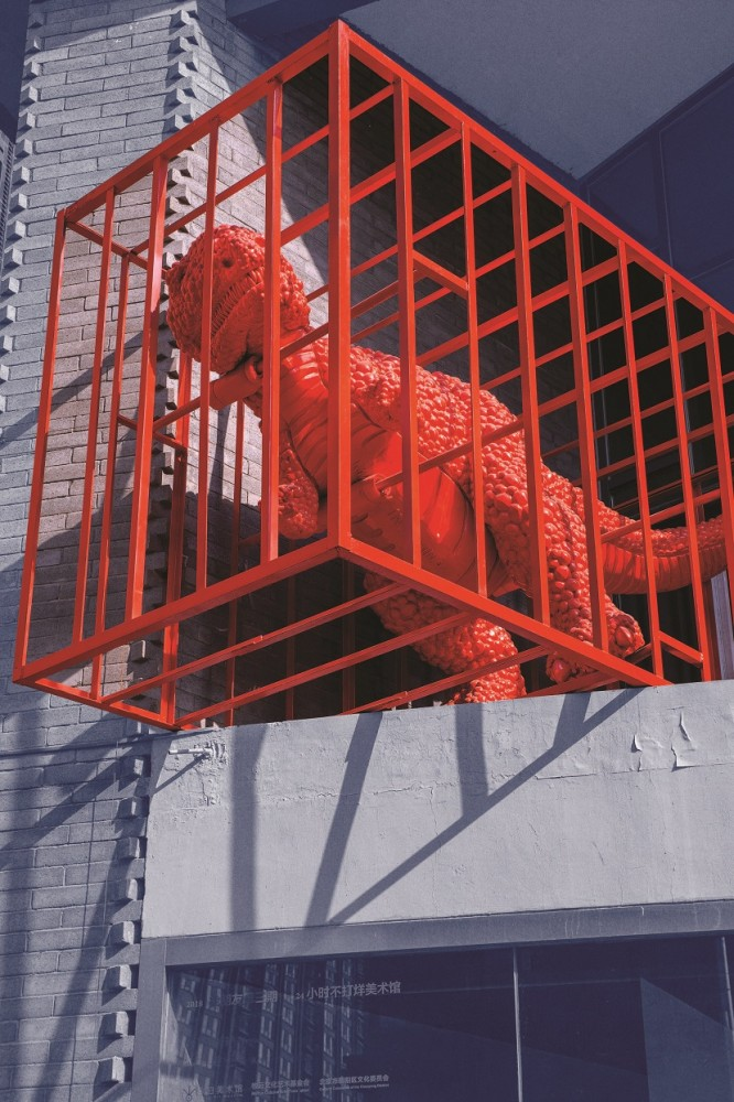 A sculpture of a red dinosaur in a cage made by artist Sui Jianguo on display in Beijing's 798 Art District.
